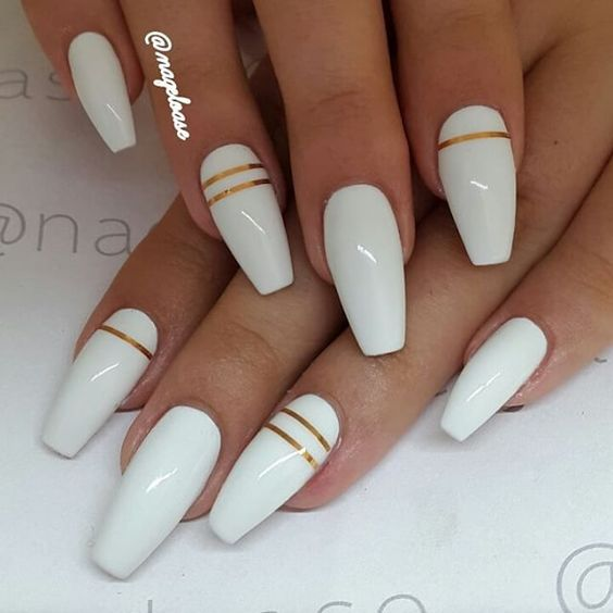 white nails with gold stripes look modern and elegant