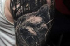 Bear and forest tattoo on the arm