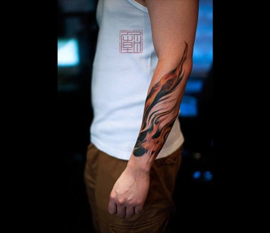 Black and orange tattoo on the arm