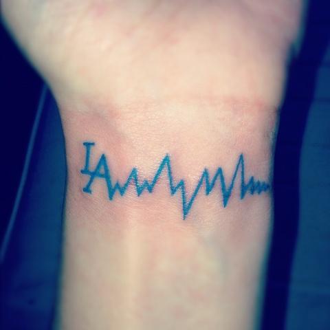 Blue tiny tattoo on the wrist