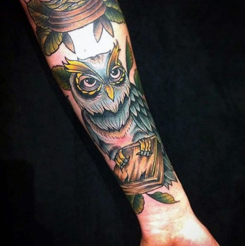 Book and owl tattoo on the hand