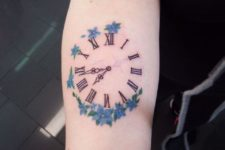 Clock with blue flowers tattoo
