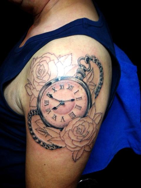 Clock with two roses tattoo on the shoulder