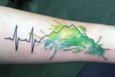 Green watercolor tattoo on the arm