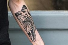 Half of tiger face tattoo on the arm