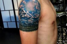 Mountain with blue sky and green forest tattoo