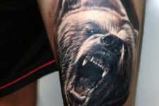 Realistic bear tattoo on the leg