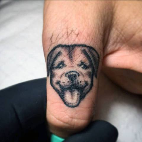 Small dog tattoo on the finger