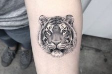 Small tiger head tattoo on the hand