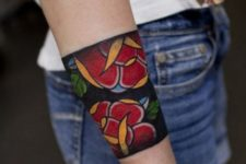 Tattoo with red flowers and green leaves