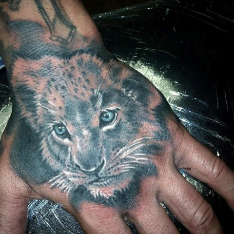 Young lion tattoo on the hand