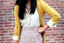 02 a pink tweed skirt, a white shirt, a mustard cardigan and strands of pearls