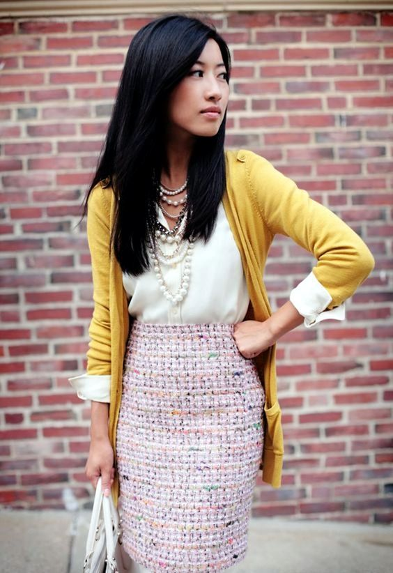 a pink tweed skirt, a white shirt, a mustard cardigan and strands of pearls