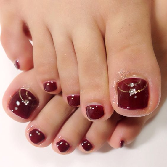 bloody red pedicute with gold glitter and rhinestones