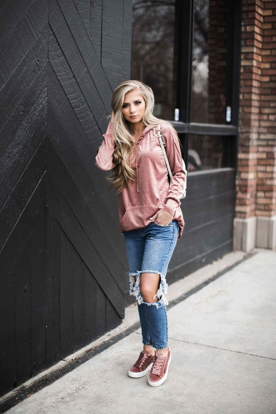 a muted pink hoodie, ripped jeans and muted pink sneakers
