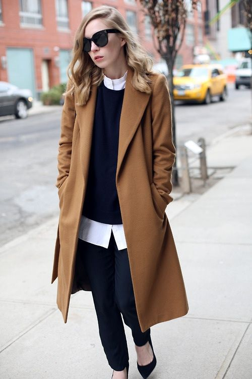 a layered look with a navy sweater and pants, a white shirt, black heels and a brown coat