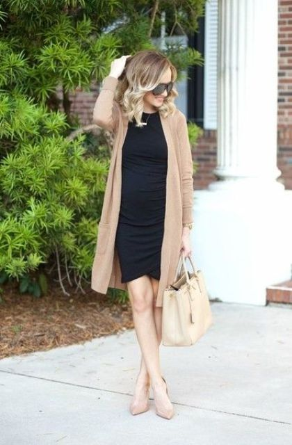 a maternity outfit with a black dress, a long neutral cardigan, nude heels and a bag