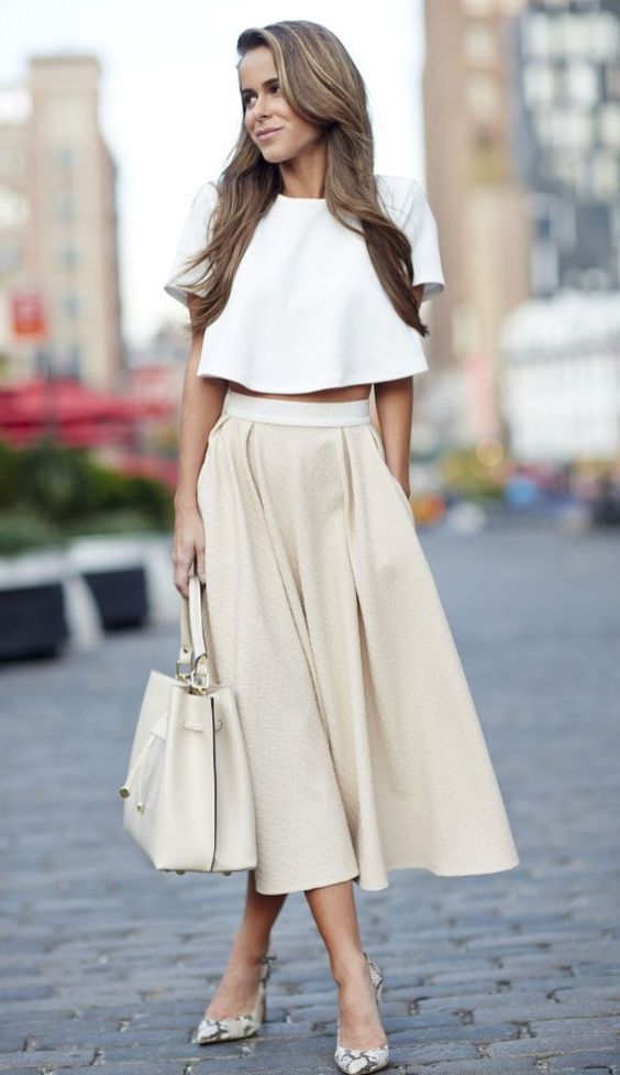a white crop top with ruffles, a neutral high waisted skirt, snake print shoes and a bag