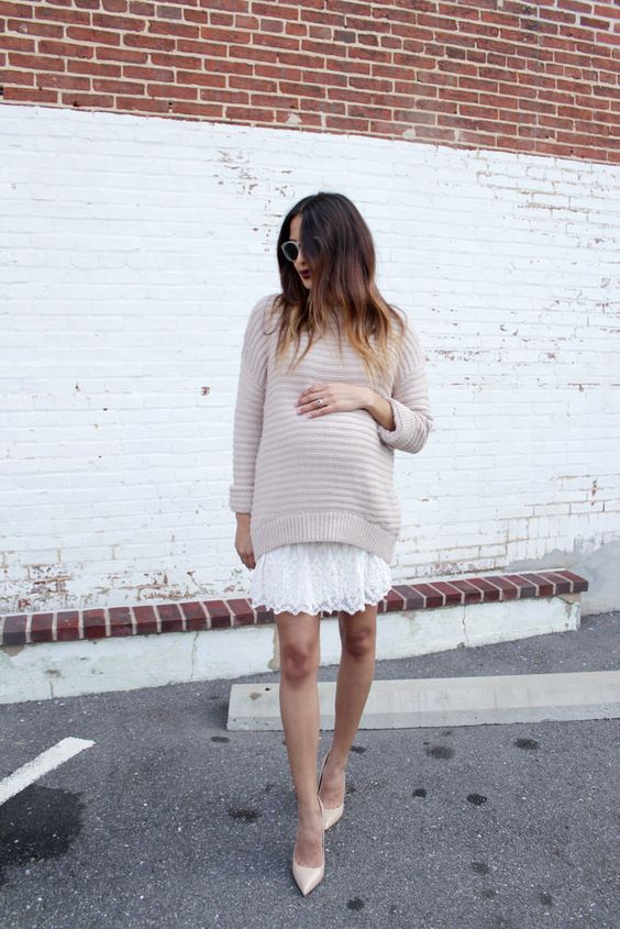 a white lace dress, a neutral sweater over it and nude pumps