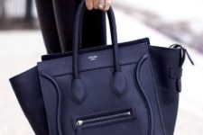 05 a chic black bag features an interesting shape that allows carrying documents