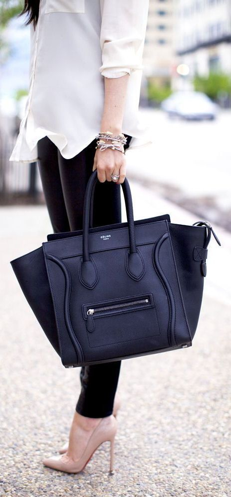 a chic black bag features an interesting shape that allows carrying documents