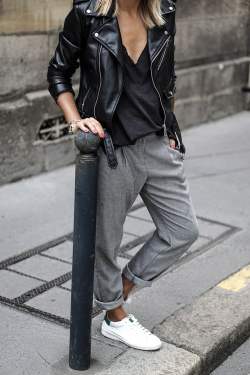 grey sporty pants, a black top, a black leather jacket and white chucks