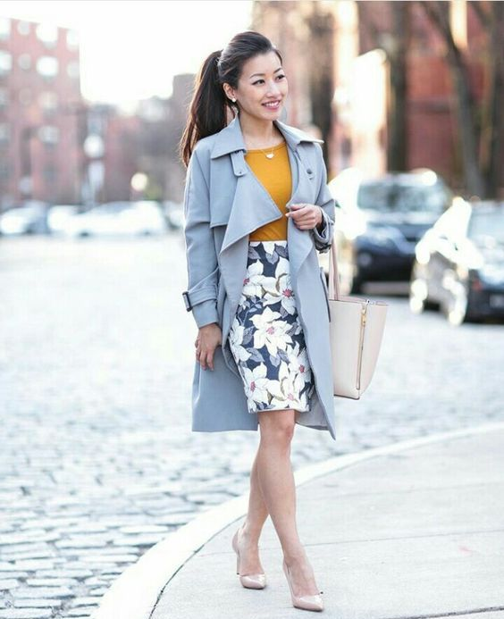 a mustard top, a floral print skirt, nude heels and a serenity blue trench coat