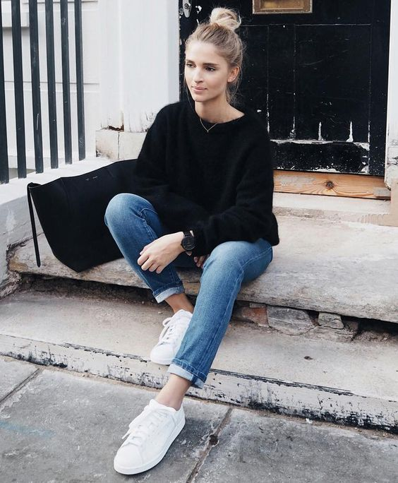 a black sweater, blue jeans, white sneakers and a black suede bag