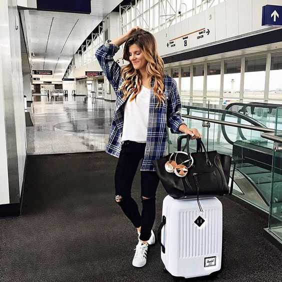a plaid shirt, a white top, black ripped jeans and white chucks for a comfy casual travel look