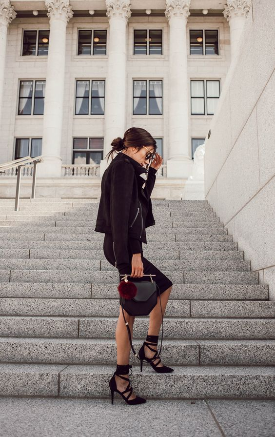 a black dress with a moto jacket, cale up heels and a cool geo bag