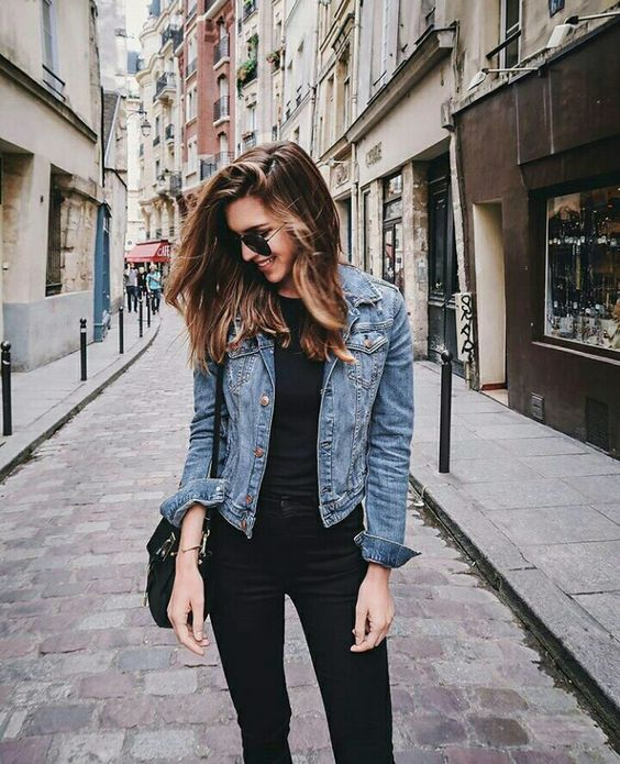 black jeans, a black t-shirt, a blue cropped denim jacket and a black bag