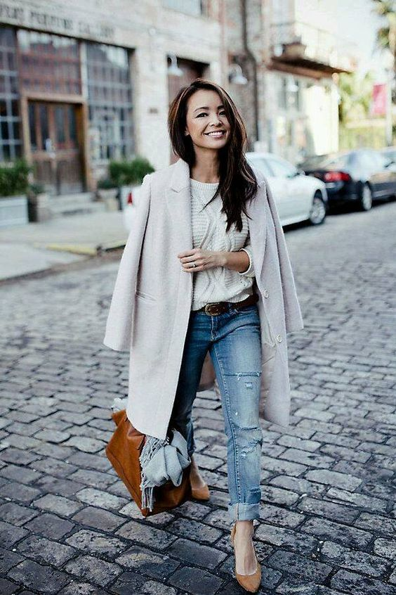 a creamy coat, a white sweater, ripped blue jeans, amber shoes and an amber bag