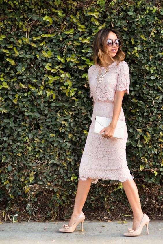 a pink lace crop top suit with a pencil skirt, nude shoes and a white clutch