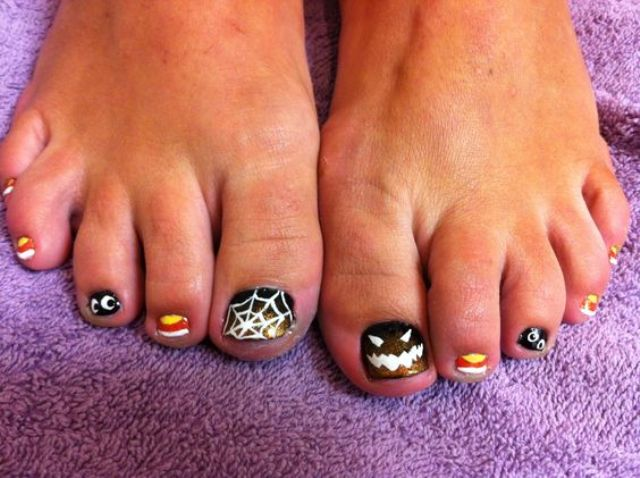 bold nails with a web, spooky eyes, a Jack-o-lantern and candy corns