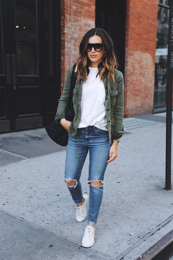 ripped jeans, a white tee, an olive green jacket and white sneakers