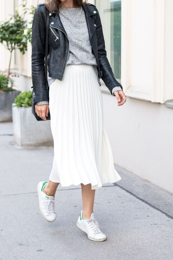 a grey tee, a white pleated midi skirt, a black leather jacket and white sneakers
