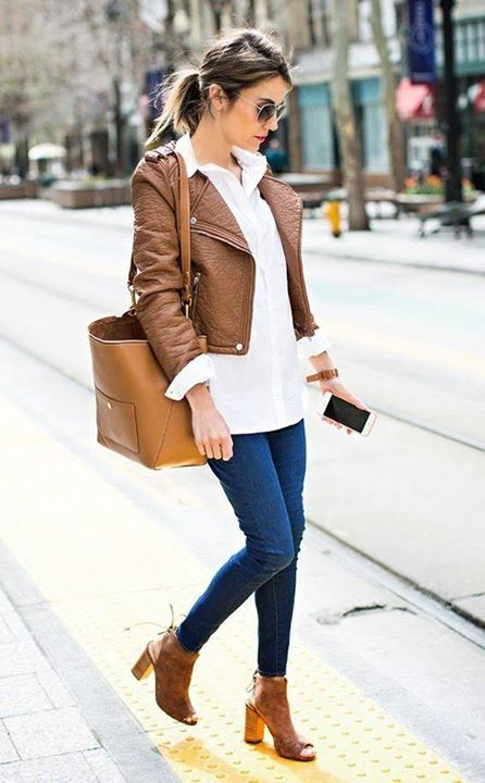a layered look with a white sweater, navy jeans, a brown leather jacket, peep toe booties and large bag