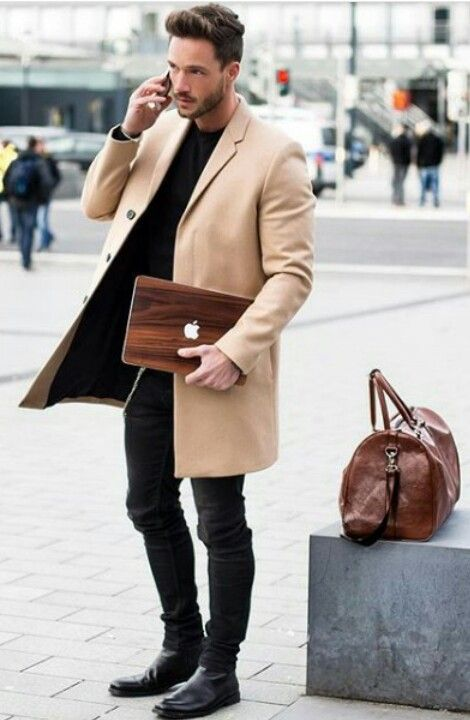 a relaxed look with a black sweater, jeans and boots and a camel coat on top