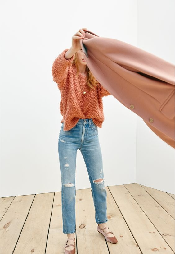 an orange chunky knit sweater, ripped jeans and pastel velvet flats