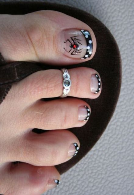 elegant French pedicure with black and white polka dots and a spider with a rhinestone