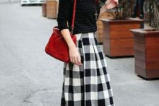 11 a striped black sweater, a plaid black and whiet skirt, black suede moccasins and a red bag