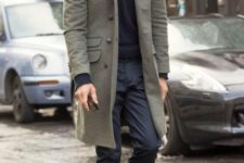 12 a black sweater, pants, amber boots and an olive green coat