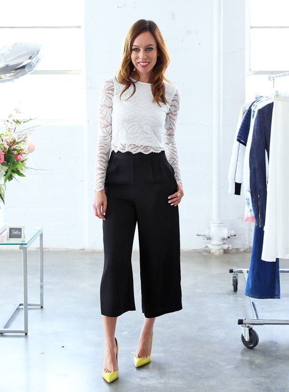 black culottes, a white lace crop top with long sleeves and neon yellow heels