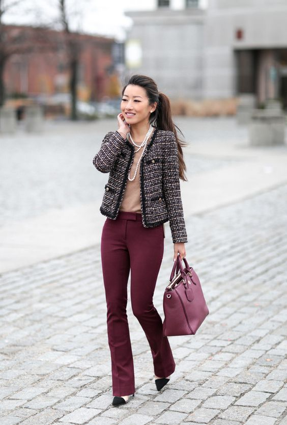 burgundy pants, a neutral top, a tweed jacket, a burgundy tote and strands of pearls