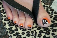 13 orange and black nails and an accent nail with a web
