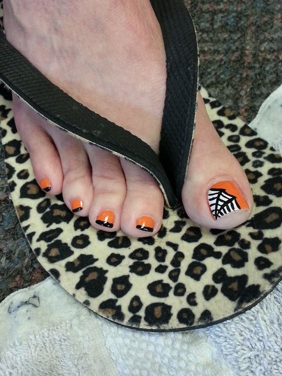 orange and black nails and an accent nail with a web