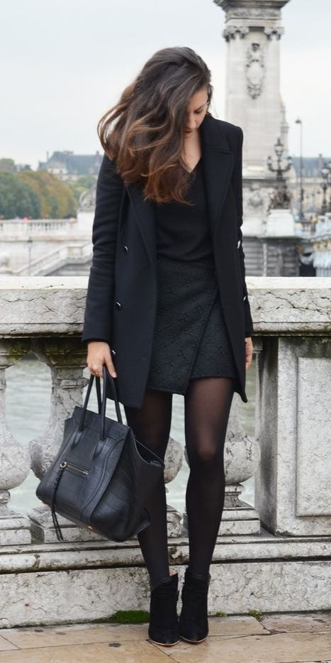 a black dress, a black coat, black suede booties and a bag