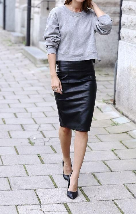 a black leather skirt, a grey sweatshirt and black heels for a classy look