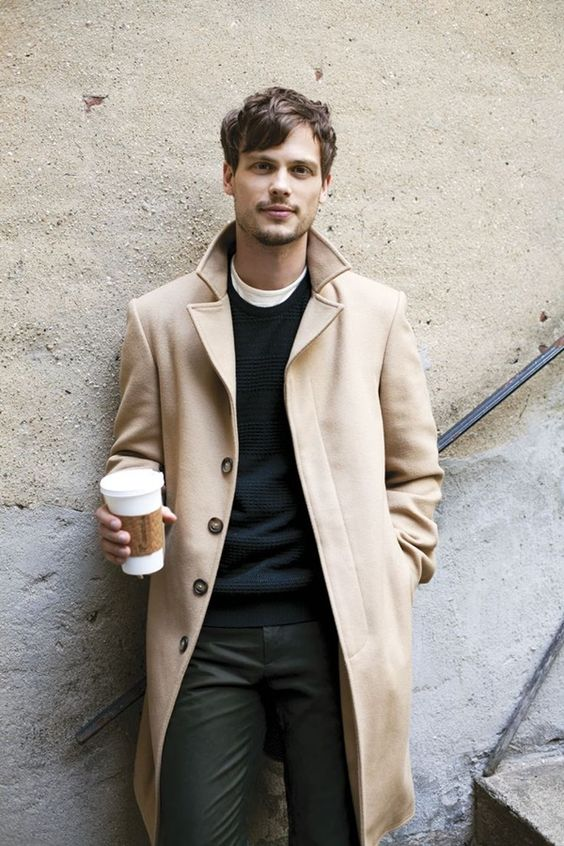 a neutral coat, olive green pants, a black sweater for a stylish layered look