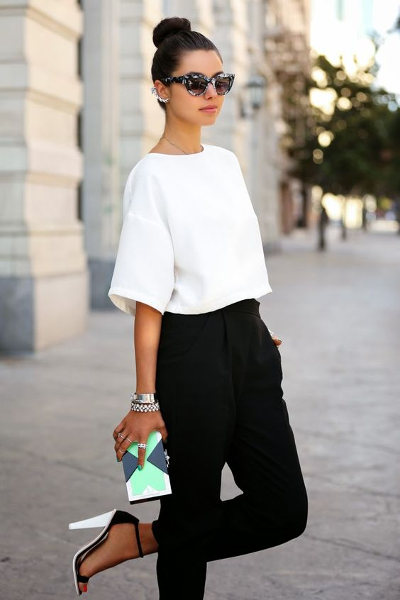 black pants, a white crop top with hald sleeves and black and white heels
